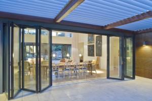 Debajo de la terraza de la casa con cristales en puertas y mucha iluminación nocturna