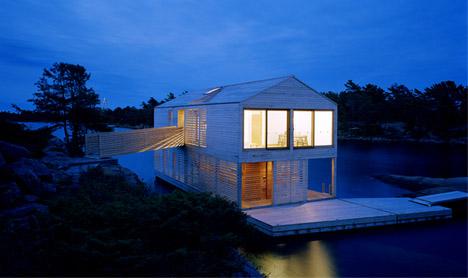 La casa de noche navegando en el agua
